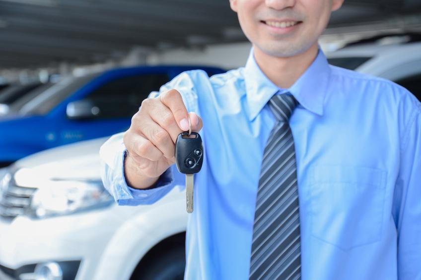 Businessman handing forward a car key and smiling